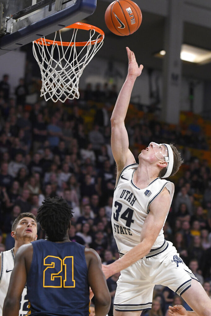 Utah State forward Justin Bean (34) shoots as North Carolina A&T forward Ronald Jackson (21) defends during the first half of an NCAA college basketball game Friday, Nov. 15, 2019, in Logan, Utah. (AP Photo/Eli Lucero)
