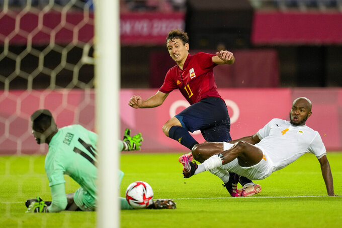 Spain's Mikel Oyarzabal takes a shot as Ivory Coast's Kouadio-Yves Dabila fails to block in a men's quarterfinal soccer match at the 2020 Summer Olympics, Saturday, July 31, 2021, in Rifu, Japan, Tokyo. (AP Photo/Andre Penner)