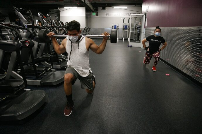 FILE - In this Friday, June 26, 2020 file photo, people wear masks while exercising at a gym in Los Angeles. On Thursday, July 9, 2020, the World Health Organization is acknowledging the possibility that COVID-19 might be spread in the air under certain conditions — after more than 200 scientists urged the agency to do so. (AP Photo/Jae C. Hong)