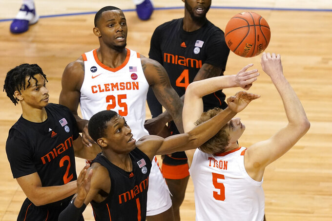 Clemson forward Hunter Tyson (5) and teammate Aamir Simms (25) look for a rebound as Miami forward Anthony Walker (1) and teammate guard Isaiah Wong (2) close in during the first half of an NCAA college basketball game in the second round of the Atlantic Coast Conference tournament in Greensboro, N.C., Wednesday, March 10, 2021. (AP Photo/Gerry Broome)