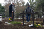 Humerto Stefanon, left, visits the gravesite of his late wife, Maria Olga Herrera, who died of COVID-19, at the Chacarita cemetery in Buenos Aires, Argentina, Tuesday, July 13, 2021. Argentina is close to reaching 100,000 deaths related to COVID-19. (AP Photo/Victor R. Caivano)