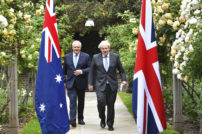 Britain's Prime Minister Boris Johnson, right, walkswith Australian Prime Minister Scott Morrison after their meeting,  in the garden of 10 Downing Streeet, in London, Tuesday June 15, 2021. Britain and Australia have agreed on a free trade deal that will be released later Tuesday, Australian Trade Minister Dan Tehan said.  (Dominic Lipinski/Pool Photo via AP)