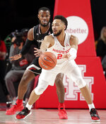 Houston guard Galen Robinson Jr., right, passes the ball in front of Cincinnati forward Trevon Scott (13) during the first half of an NCAA college basketball game Sunday, Feb. 10, 2019, in Houston. (AP Photo/Michael Wyke)