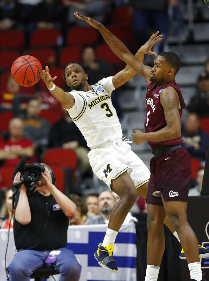 Michigan guard Zavier Simpson passes in front of Montana guard Sayeed Pridgett, right, during a first round men's college basketball game in the NCAA Tournament, Thursday, March 21, 2019, in Des Moines, Iowa. (AP Photo/Charlie Neibergall)