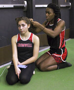 FILE - In this Feb. 7, 2019 file photo, Cromwell High School transgender athlete Andraya Yearwood, right, braids the hair of teammate Taylor Santos during a break at a track meet at Hillhouse High School in New Haven, Conn. Between 2017 and 2019, transgender sprinters Yearwood and Terry Miller combined to win 15 championship races, prompting a lawsuit on behalf of four cisgender girls. (AP Photo/Pat Eaton-Robb, File)