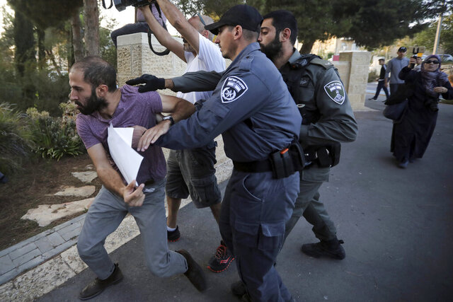 FILE - In this Oct. 1, 2019 file photo, Israeli police push a man during a protest outside a hospital in Jerusalem where Samir Arbeed, a Palestinian suspect in a deadly West Bank bombing, is being treated. Israel faces allegations of severely torturing three alleged Palestinian militants rounded up after the rare bombing in the occupied West Bank killed a 17-year-old girl in August. Lawyers and family members say the three top suspects were severely beaten to the point of being hospitalized before being returned to their interrogators. A Supreme Court ruling in 1999 forbids torture, but Israeli and Palestinian rights groups say interrogators routinely exploit a loophole intended for rare, ticking time-bomb scenarios, and act with impunity. (AP Photo/Mahmoud Illean, File)