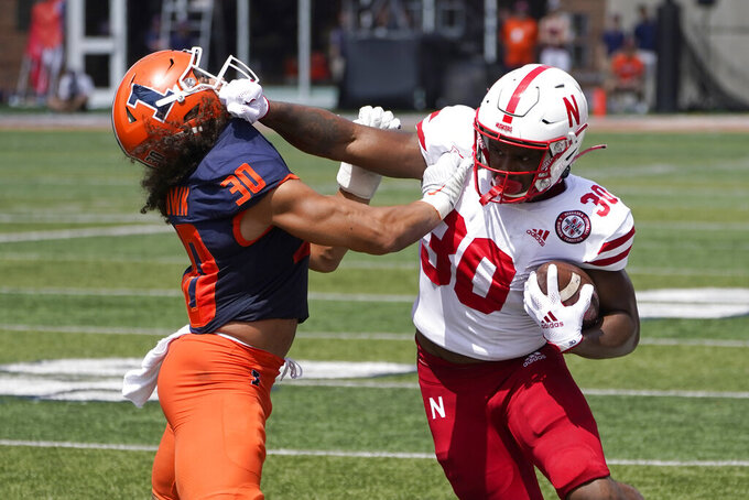 Nebraska running back Markese Stepp, right, stiff arms Illinois's Sydney Brown during the first half of an NCAA college football game Saturday, Aug. 28, 2021, in Champaign , Ill. (AP Photo/Charles Rex Arbogast)