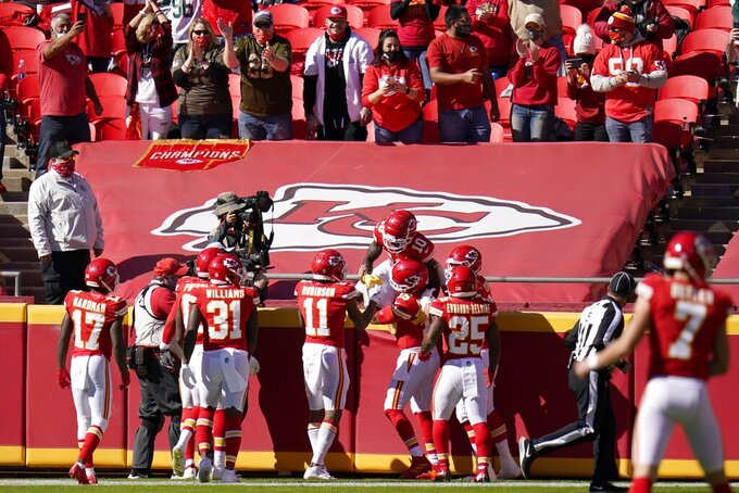 Fans cheer after Kansas City Chiefs players celebrate with Tyreek Hill (10) who caught a pass for a touchdown in the first half of an NFL football game against the New York Jets on Sunday, Nov. 1, 2020, in Kansas City, Mo. (AP Photo/Jeff Roberson)