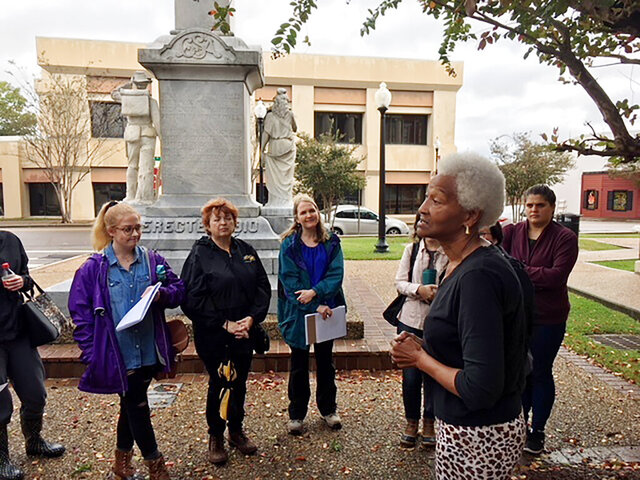 In this Oct. 26, 2019, photo provided by the University of Southern Mississippi (USM), Lillie Easton, foreground, a resident of Palmer's Crossing community in Hattiesburg, Miss.,, talks to USM students about the history of the civil rights movement in the area during a field trip in the city. Students took part in the trip as part of a USM history program class focused on the civil rights movement in Mississippi. In the background is the Civil War monument next to the Forrest County Courthouse, the county seat. (David Tisdale/University of Southern Mississippi via AP)