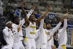The Northern Kentucky bench, including forward Adrian Nelson (4), celebrate during the second half of an NCAA college basketball game against Illinois-Chicago for the Horizon League men's tournament championship in Indianapolis, Tuesday, March 10, 2020. Northern Kentucky won 71-62. (AP Photo/Michael Conroy)