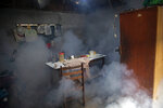 Clouds of insecticide seep into a dining room during a fumigation operation to help control the spread of dengue fever, in downtown Pucallpa, Peru, Tuesday, Sept. 29, 2020. As Peru grapples with one of the world's worst COVID-19 outbreaks, another epidemic is starting to raise alarm: Dengue. (AP Photo/Rodrigo Abd)