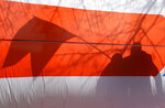 People cast shadows on opposition flag during celebration in Minsk, Belarus, Sunday, March 24, 2019, on the eve of March 25, a traditional day of demonstration for the opposition.  Many people gather to mark what they call Freedom Day, on the 101st anniversary of the 1918 declaration of the first, short-lived independent Belarus state, the Belarusian People's Republic lasted until 1919. (AP Photo/Sergei Grits)