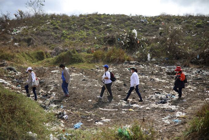 FILE - In this March 11, 2019 file photo, members of the Solecito Collective, who are seeking their missing loved ones, look for signs of clandestine graves at a municipal dump after an anonymous source sent the group a map  suggesting hundreds of bodies were buried in the area, in the port city of Veracruz, Mexico. The mainly female volunteer searchers who fan out across Mexico to dig for the bodies of their murdered relatives are themselves increasingly being killed, putting to the test the government's promise to help them in their quest for a final shred of justice: a chance to mourn.  (AP Photo/Felix Marquez, File)