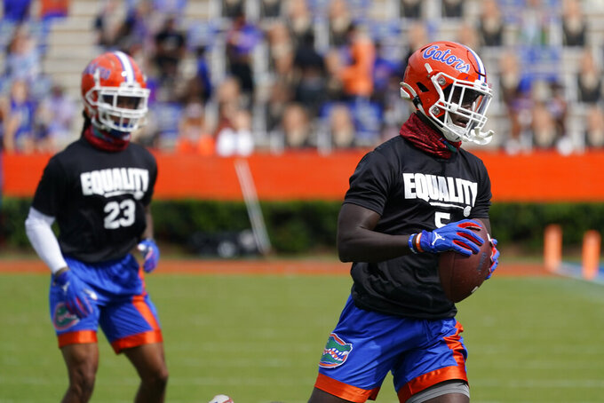 Florida defensive back Jaydon Hill (23) and defensive back Kaiir Elam (5) wear shirts with the social justice message Equality during warm ups before an NCAA college football game against South Carolina, Saturday, Oct. 3, 2020, in Gainesville, Fla. (AP Photo/John Raoux,Pool)