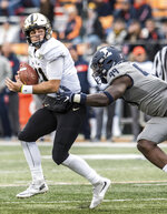 Purdue quarterback David Blough (11) looks to pass as he is pressured by Illinois' Owen Carney (99) in the second half of an NCAA college football game, Saturday, Oct. 13, 2018, in Champaign, Ill. (AP Photo/Holly Hart)