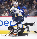 St. Louis Blues' Vince Dunn (29), Vancouver Canucks' Adam Gaudette (88) and referee Ian Walsh collide during the second period of an NHL hockey game Tuesday, Nov. 5, 2019, in Vancouver, British Columbia. (Darryl Dyck/The Canadian Press via AP)