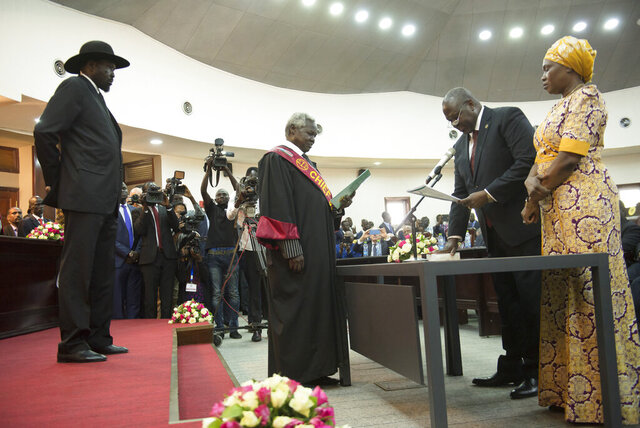 The president of South Sudan, Salva Kiir Mayardit, left, swears in Dr. Riek Machar as the first Vice President of South Sudan, in Juba, South Sudan Saturday, Feb. 22, 2020. South Sudan opened a new chapter in its fragile emergence from civil war Saturday as rival leaders formed a coalition government. (AP Photo/Charles Atiki Lomodong )