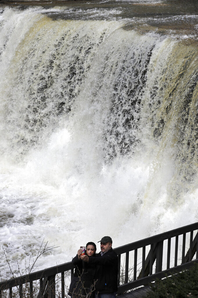 Anna and Johnny Hassouneh take a selfie at the waterfall, Wednesday, April 1, 2020, in Chagrin Falls, Ohio. (AP Photo/Tony Dejak)