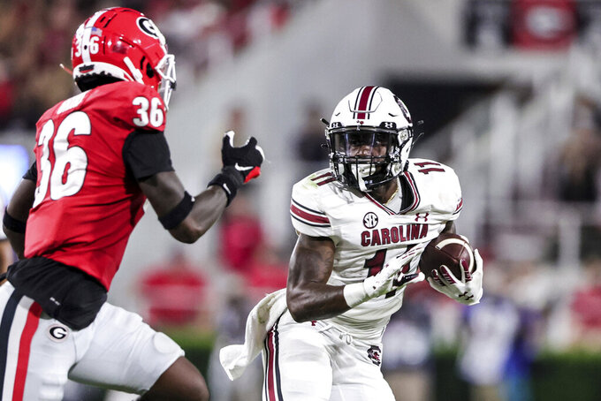 South Carolina running back ZaQuandre White (11) carries the ball as Georgia defensive back Latavious Brini (36) pursues during the second half of an NCAA college football game Saturday, Sept. 18, 2021, in Athens, Ga. Georgia won 40-13. (AP Photo/Butch Dill)