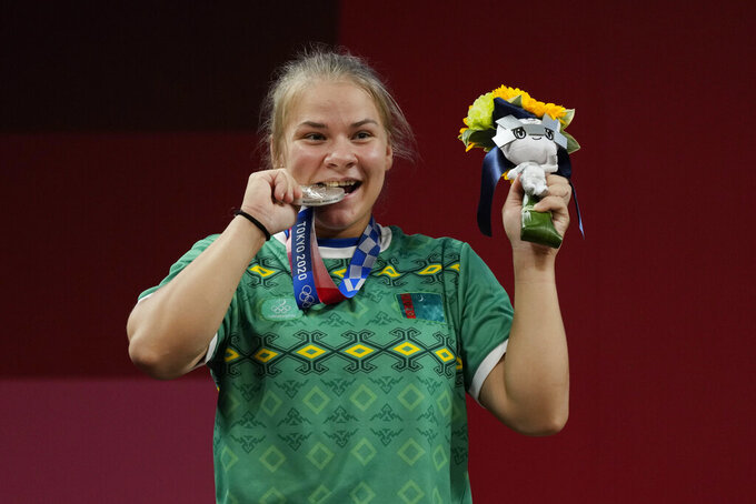 Polina Guryeva of Turkmekistan celebrates on the podium after winning the silver medal in the women's 59kg weightlifting event, at the 2020 Summer Olympics, Tuesday, July 27, 2021, in Tokyo, Japan. She won gold medal and sets a new Olympic record. (AP Photo/Luca Bruno)