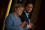 German Chancellor Angela Merkel, left, and Dutch Prime Minister Mark Rutte answer questions after a meeting in The Hague, Netherlands, Wednesday, Oct. 10, 2018. The two leaders met ahead of next week's crucial EU summit in Brussels. (AP Photo/Peter Dejong)