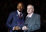 Naismith Memorial Basketball Hall of Famer Ray Allen, left, is presented with a plaque by coach and Basketball Hall of Famer Jim Calhoun, right, in a halftime ceremony during which Allen's number was retired to the rafters at an NCAA college basketball game between South Florida and Connecticut, Sunday, March 3, 2019, in Storrs, Conn. (AP Photo/Steven Senne)