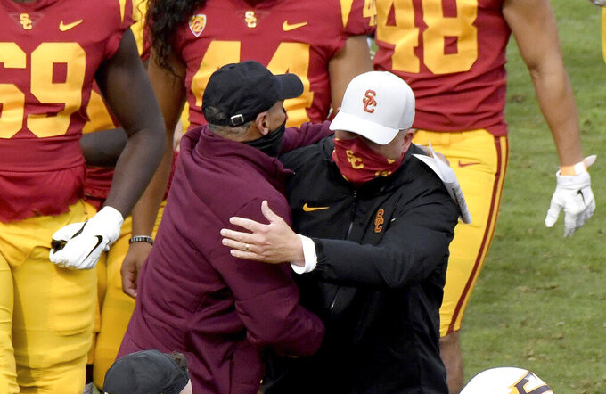 Arizona State head coach Herm Edwards, left, congratulates Southern California head coach Clay Helton  after an NCAA college football game in Los Angeles, Saturday, Nov. 7, 2020. (Keith Birmingham/The Orange County Register via AP)