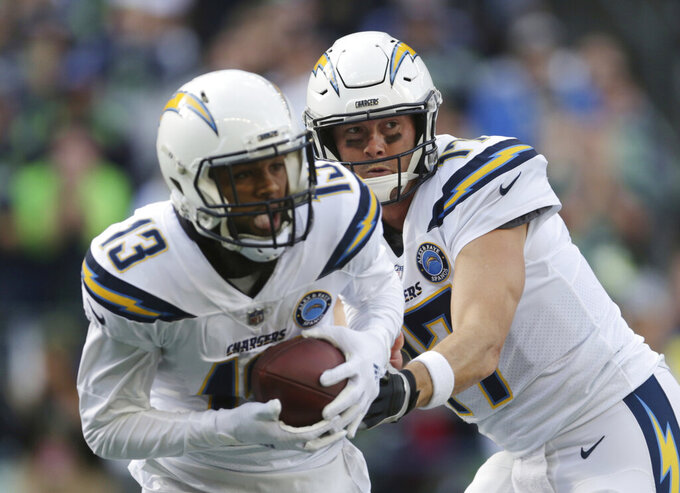 FILE - In this Nov. 4, 2018, file photo, Los Angeles Chargers quarterback Philip Rivers, right, hands off to Keenan Allen during the first half of the team's NFL football game against the Seattle Seahawks in Seattle. Rivers has a talented receiving corps with Allen, Mike Williams and Travis Benjamin as well as getting back Hunter Henry, who missed the regular season with a knee injury. (AP Photo/Scott Eklund, File)