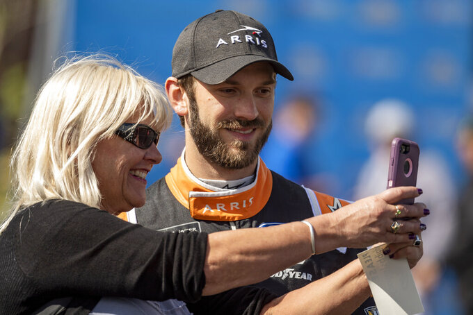 Driver Daniel Suarez takes selfing with a fan before the  NASCAR Xfinity Series auto race, Saturday, Oct. 5, 2019, in Dover, Del. (AP Photo/Brien Aho)