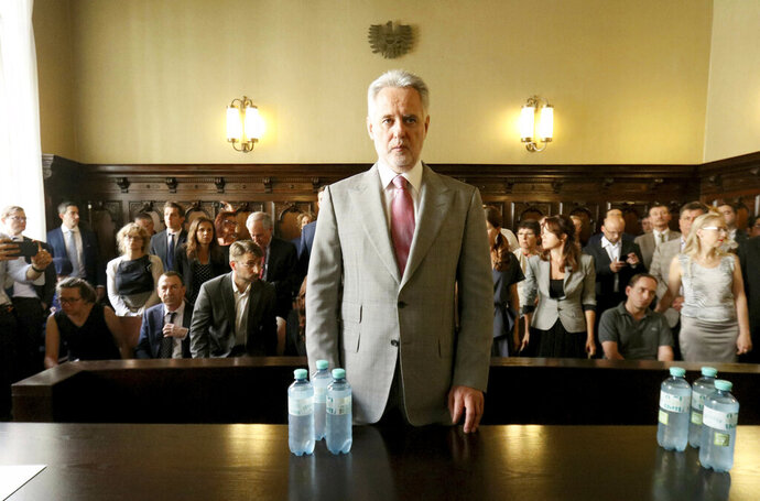 FILE - In this Tuesday, June 25, 2019 file photo, Ukrainian oligarch Dymitro Firtash waits for the start of his trial at the Austrian supreme court in Vienna, Austria. Austrian officials say the country's justice minister has approved the extradition to the U.S. of Firtash, but his defense has filed a court application to reopen the case and he can stay in Austria for now. Last month, Austria's Supreme Court of Justice upheld a previous ruling that Firtash can be extradited to face an indictment accusing him of a conspiracy to pay bribes in India to mine titanium. Firtash denies wrongdoing. (AP Photo/Ronald Zak, File)