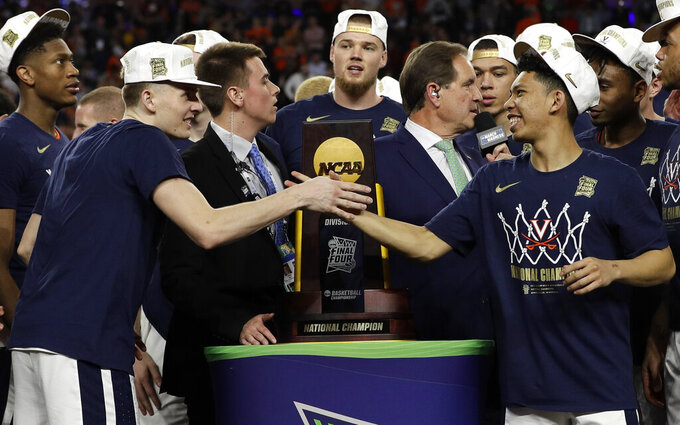 Virginia's Kyle Guy, left, and Kihei Clark shake hands in front of the championship trophy as they celebrate after defeating Texas Tech 85-77 in the overtime in the championship of the Final Four NCAA college basketball tournament, Monday, April 8, 2019, in Minneapolis. (AP Photo/David J. Phillip)