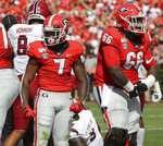Georgia tailback D'Andre Swift (left) and offensive lineman Solomon Kindley flex after Swift powered his way into the endzone for a 1-yard touchdown run to take a 10-7 lead over South Carolina during the second quarter in a NCAA college football game on Saturday, October, 12, 2019, in Athens. (Curtis Compton/Atlanta Journal-Constitution via AP)