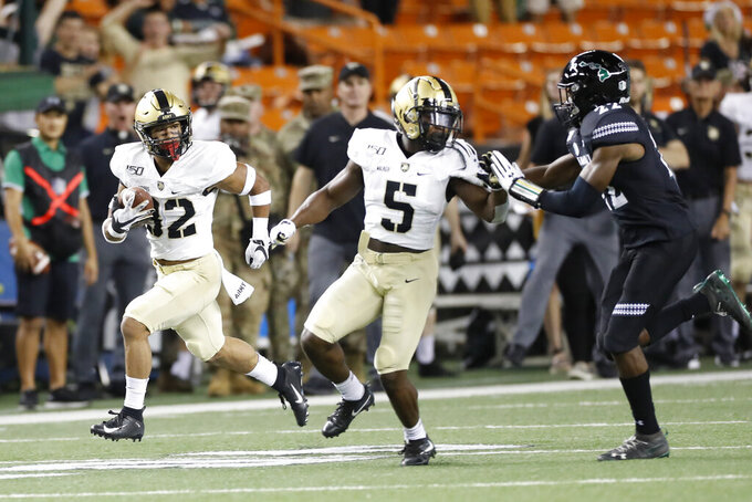 As Army running back Kell Walker (5) blocks Hawaii defensive back Ikem Okeke (22), Army running back Artice Hobbs IV (32) runs down the field during the first half of an NCAA college football game Saturday, Nov. 30, 2019, in Honolulu. (AP Photo/Marco Garcia)