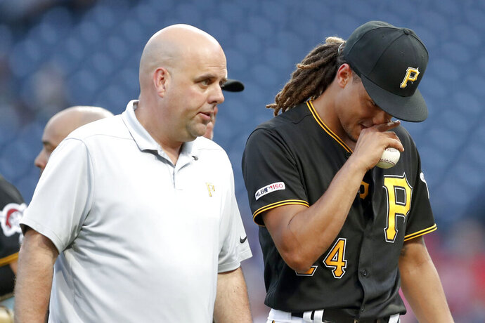 Pittsburgh Pirates starting pitcher Chris Archer, right, leaves the field with trainer Bryan Housand before the start of the second inning in a baseball game against the Washington Nationals, Tuesday, Aug. 20, 2019, in Pittsburgh. (AP Photo/Keith Srakocic)