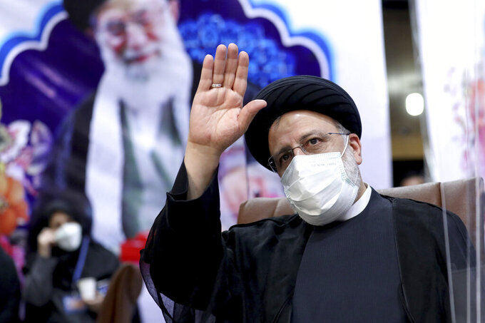 FILE - In this May 15, 2021 file photo, Ebrahim Raisi, then head of Iran's judiciary, waves to journalists while registering his candidacy for the upcoming presidential elections, in Tehran, Iran. Once President-elect Raisi, a protégé of Iran's Supreme Leader Ayatollah Ali Khamenei, shown in background, is sworn in as president this week, hard-liners will control all parts of the Islamic Republic's civilian government. Iran's inauguration of Raisi on Thursday represents the last stop in a slow slide from the hopes that the 2015 nuclear deal would open the Islamic Republic to the West. (AP Photo/Ebrahim Noroozi, File)