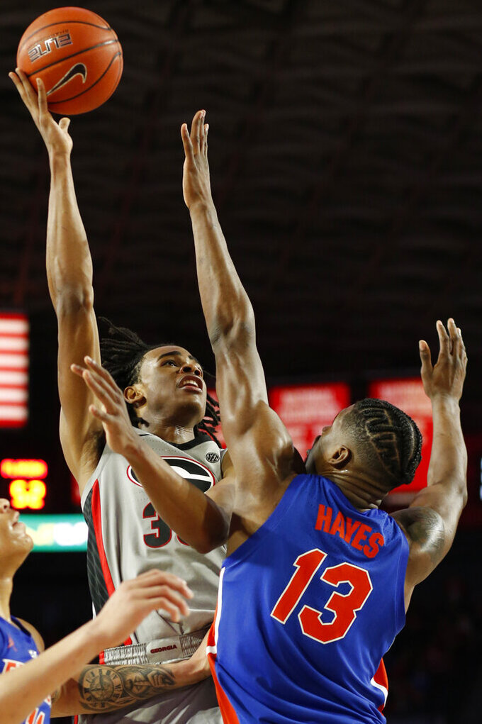 Georgia forward Nicolas Claxton (33) takes a shot over Florida center Kevarrius Hayes (13)  during an NCAA college basketball game in Athens, Ga., on Saturday, Jan. 19, 2019.  ( Joshua L. Jones/Athens Banner-Herald via AP)