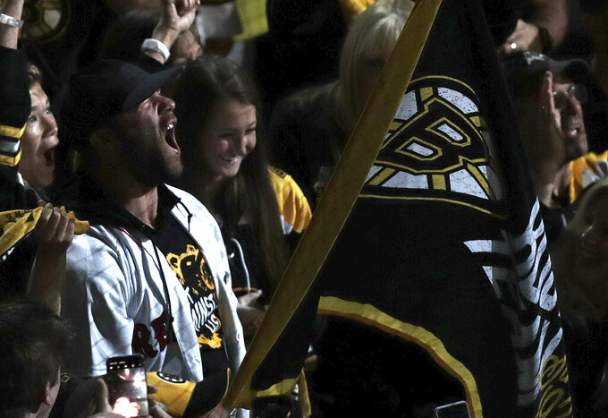 New England Patriots' Julian Edelman, left, roars as he waves the Boston Bruins banner before Game 7 of the NHL hockey Stanley Cup Final between the Bruins and the St. Louis Blues, Wednesday, June 12, 2019, in Boston. (AP Photo/Charles Krupa)
