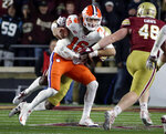 Clemson quarterback Trevor Lawrence (16) is dragged down by a Boston College defender during the first half of an NCAA college football game Saturday, Nov. 10, 2018, in Boston. (AP Photo/Elise Amendola)