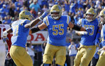 UCLA running back Joshua Kelley, left, celebrates his rushing touchdown with teammates Michael Alves (55) and Jake Burton during the first half of an NCAA college football game Saturday, Nov. 24, 2018, in Pasadena, Calif. (AP Photo/Marcio Jose Sanchez)
