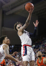 Gonzaga guard Josh Perkins, center, shoots between teammate Brandon Clarke, left, and Pacific guard Brandon McGhee during the first half of an NCAA college basketball game in Spokane, Wash., Thursday, Jan. 10, 2019. (AP Photo/Young Kwak)