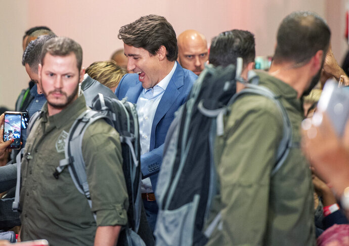 High profile security surrounds Liberal Leader Justin Trudeau as he arrives at a rally in Mississauga, Ontario, Saturday, Oct. 12, 2019. The rally was delayed for 90 minutes due to a security issue. (Frank Gunn/The Canadian Press via AP)