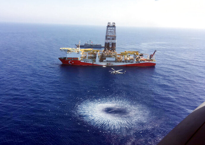 In this Tuesday, July 9, 2019 photo, a helicopter flies over Turkey's drilling ship, 'Fatih' dispatched towards the eastern Mediterranean, near Cyprus. Turkish officials say the drillships Fatih and Yavuz will drill for gas, which has prompted protests from Cyprus. (Turkish Defence Ministry via AP, Pool)