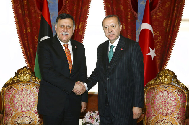 FILE - In this Monday, Feb. 26, 2018, file photo, Turkish President Recep Tayyip Erdogan, right, shakes hands with Fayez al-Sarraj, the Chairman of the Libyan Presidential Council, shortly before departing for a five-day African tour, in Istanbul. The U.S. Defense Department's inspector general says Turkey has sent between 3,500 and 3,800 paid Syrian fighters to Libya over the first three months of 2020. (Kayhan Ozer/Pool Photo via AP, File)