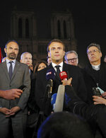French Prime Minister Edouard Philippe, left, French President Emmanuel Macron, and Archbishop of Paris, Michel Aupetit, right, answer reporters after watching the fire at Notre Dame cathedral in Paris, Monday, April 15, 2019. A catastrophic fire engulfed the upper reaches of Paris' soaring Notre Dame Cathedral as it was undergoing renovations Monday, threatening one of the greatest architectural treasures of the Western world as tourists and Parisians looked on aghast from the streets below.(Philippe Wojazer/Pool via AP)