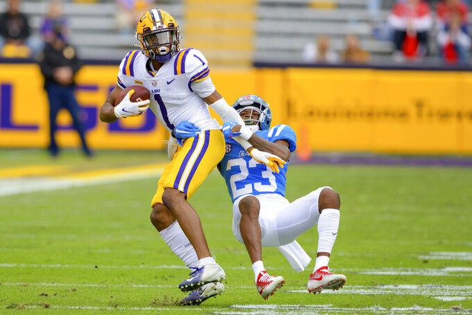 LSU wide receiver Kayshon Boutte (1) runs after a reception against Mississippi defensive back Jakorey Hawkins (23) during the first half of an NCAA college football game in Baton Rouge, La., Saturday, Dec. 19, 2020. (AP Photo/Matthew Hinton)