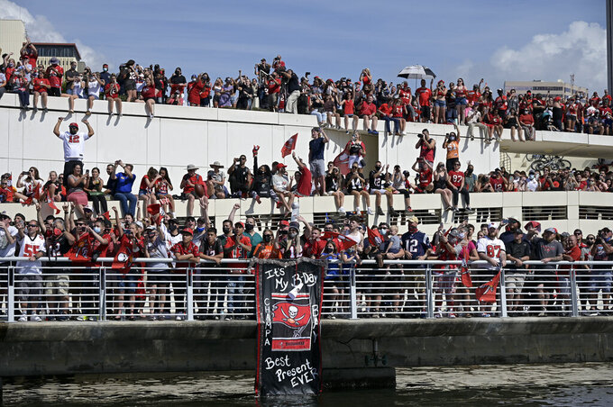 Fans watch the Tampa Bay Buccaneers celebrate their Super Bowl 55 victory over the Kansas City Chiefs with a boat parade in Tampa, Fla., Wednesday, Feb. 10, 2021. (AP Photo/Phelan Ebenhack)
