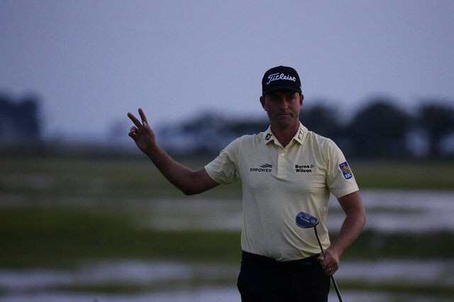 Webb Simpson waves as the sun disappears on the 18th green, on a course with no fans due to the COVID-19 pandemic, during the final round of the RBC Heritage golf tournament, Sunday, June 21, 2020, in Hilton Head Island, S.C. (AP Photo/Gerry Broome)