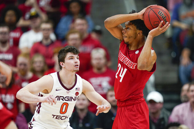 Louisville forward Dwayne Sutton (24) passes the ball around Virginia Tech guard Hunter Cattoor (0) during the first half of an NCAA college basketball game, Sunday, March 1, 2020, in Louisville, Ky. (AP Photo/Bryan Woolston)