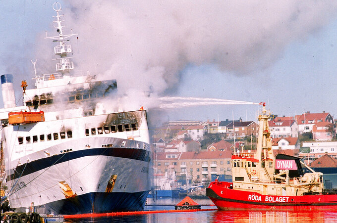 FILE - In this April 8, 1990 file photo, clouds of smoke float over the town and harbor of Lysekil, Sweden, as fire fighters struggle to extinguish the fire on the Scandinavian Star. Danish lawmakers have decided to create a task force to look into a 1990 ferry fire that killed 159 people, it was announced Wednesday, May 12, 2021. The Scandinavian Star was engulfed in flames on an overnight run from the Norwegian capital of Oslo to northern Denmark on April 7, 1990. Arson was initially blame, however a report concluded that the 20-year-old ferry had been unfit to sail.(AP Photo/Peter Dejong, file)