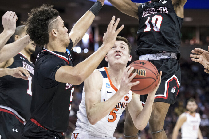 Virginia guard Kyle Guy (5) attempts a shot against Gardner-Webb guard Jose Perez (5) during a first-round game in the NCAA men's college basketball tournament Friday, March 22, 2019, in Columbia, S.C. Virginia defeated Gardner-Webb 71-56. (AP Photo/Sean Rayford)